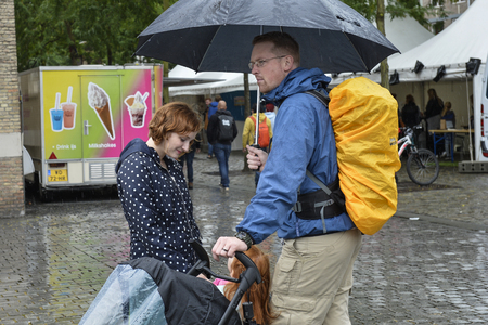 breda: Breda, The Netherlands - September 5, 2015: A young family with red overhear under an umbrella is exposing on the RedHead Days. Editorial