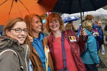 breda: Breda, The Netherlands - September 5, 2015: Three ladies with red overhear under umbrellas are exposing on the RedHead Days. Editorial
