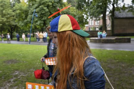 breda: Breda, The Netherlands - September 5, 2015: Young lady with red hear and colored cap is exposing on the RedHead Days.