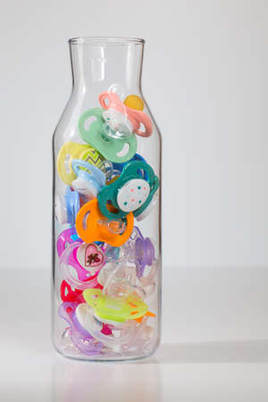some colorful pacifiers in a large glass bottle with white background.