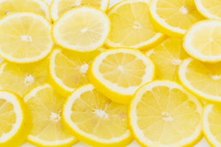 Some vitamin rich lemons cut and placed side by side as a background. Horizontal