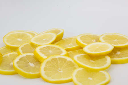 Many healthy and vitamin-rich lemon slices lined up and stacked with white background. Horizontal format with some copy space