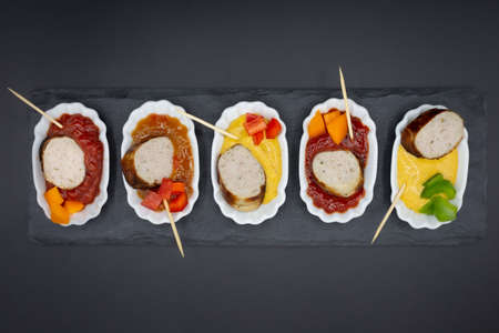 small plates with bratwurst and different sausages plus various dips. Arranged in a row with black background