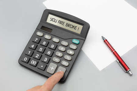 Person charged assets and money with calculator and gets indicated that he is broke. Horizontal with pen and paper