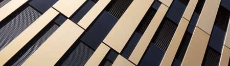Abstract house facade with gold and black pattern and sun reflection usable as background for architecture or art topics. Horizontal, panoramic Reklamní fotografie