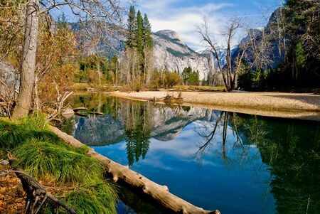 The Merced River flows past Sycamores with Half Dome and North Dome in the backgrouns.