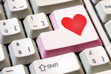 enter key: Love is the key. Heart on a pink computer enter key. Stock Photo