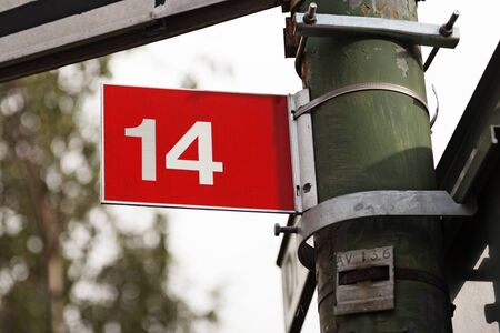 the number fourteen on a red sign with white text Stock Photo