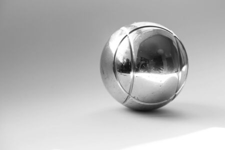 a silver Boule globe lies on a light background with ghost reflections