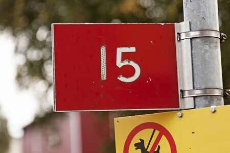 the number fifteen with white text on the red bottom and do not let the dog poop sign
