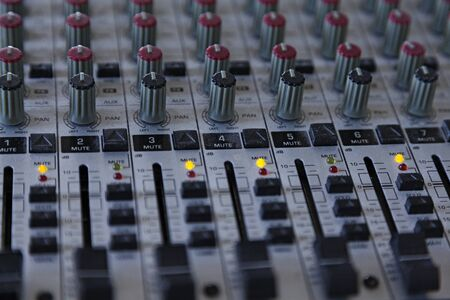 dusty studio and mixing desk for sound and music, lots of buttons and knobs Фото со стока