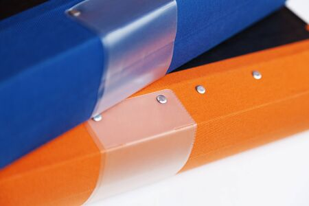 an orange and a blue binder lying in a pile in the office
