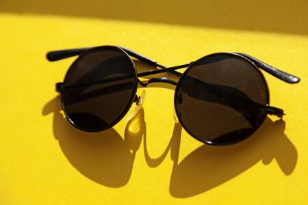 sunglasses lying in the sun on yellow surface, seventy model