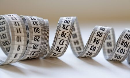 a white tape measure lying in a tangled spiral on the table