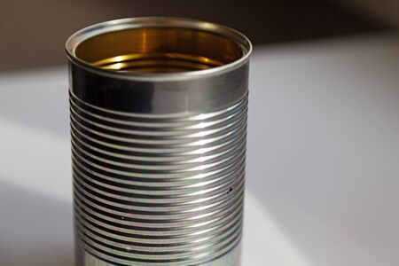 a tin can that is empty and stands on the kitchen table