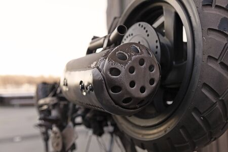 the rear wheel and exhaust pipe on a broken moped Stock Photo