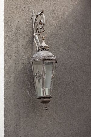 very old lantern with candles hanging on gray concrete wall 免版税图像