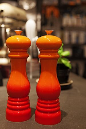 salt and pepper mill in orange color on table
