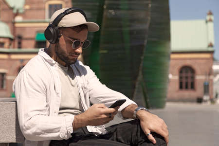Umea, Norrland Sweden - June 19, 2020: young man sitting and looking at his mobile phone