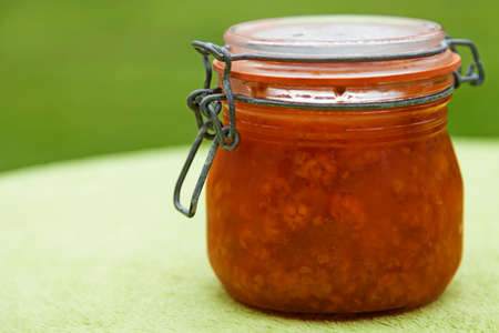 a glass jar with cloudberry jam on green background