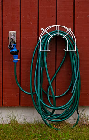 green water hose hanging on wall