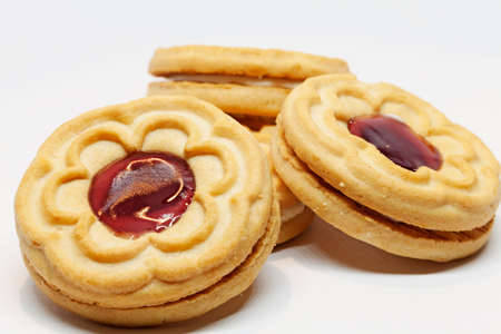 several biscuits with jam in the middle on white background