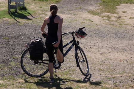 Umea, Norrland Sweden - June 10, 2020: woman stretches her legs before cycling up the mountain Redakční