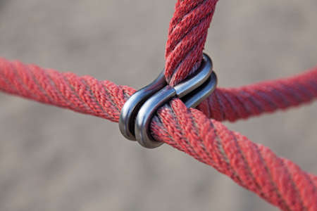 two red thick ropes are attached with metal ring