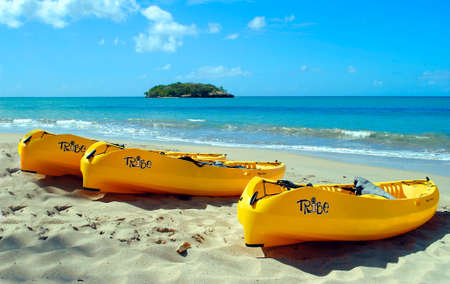 Halcyon Beach in St Lucia in the eastern Caribbean Sea, Part of the Lesser Antilles  JANUARY 28 2012  Three canoes on the silver white sand beach for a tropical vacation at Sandals Luxury Hotel