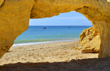 armacao: Natural stone arch on Armacao De Pera Beach with dolphins swimming