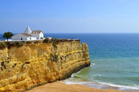 barlavento: The Chapel of Nossa Senhora da Rocha  on top of the spectacular cliffs on Nova Beach in Portugal