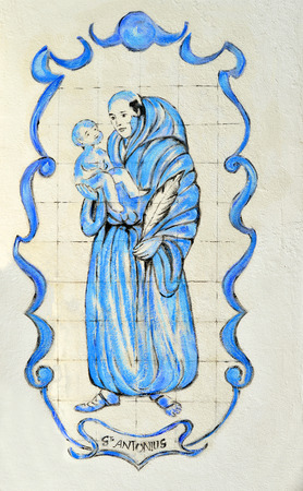 depicting: Tiles depicting a priest with a child outside St Anthony