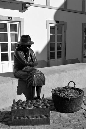 monchique: Statue of a lady selling fruit in Querenca in the Serra de Monchique mountain range of the Algarve, Portugal Editorial