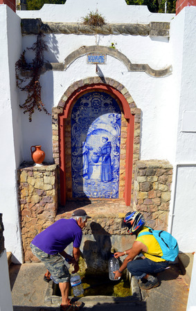 alte: Alte, Algarve, Portugal - October 6, 2014: Two men filling bottles from a spring water drinking fountain
