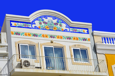 hinterland: Floral tiles on the front of a house with a balcony in Loule