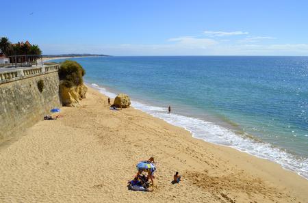 armacao: Tourists enjoying sunny weather on Armacao De Pera Beach on the Algarve coast Stock Photo
