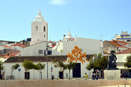 barlavento: Lagos, Algarve, Portugal - October 28, 2015 : The historical Santa Maria Church bell tower in the background and the Statue of Henry the Navigator in the foreground in Lagos center