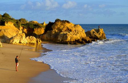 algarve: October 28, 2015 : Sietskes Beach, Algarve, Portugal. Men fishing from Sietskes Beach on the Algarve coast Editorial