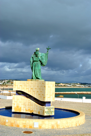 barlavento: Lagos, Algarve, Portugal - October 28, 2015 : Statue of the Portuguese Patron Saint of fishermen in the Algarve S. Goncalo de Lagos looking out towards the stormy weather