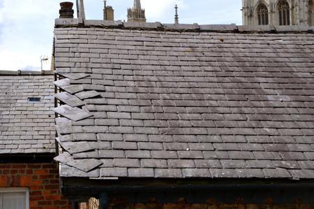 undone: Loose slates on a house roof