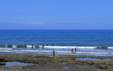 passtime: Playa De Las Americas beach, Tenerife, Canary Islands, Spain, Europe - June 12, 2016 : Surfing on Playa De Las Americas beach Stock Photo
