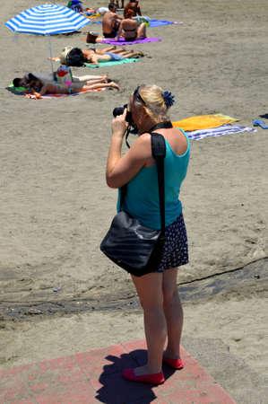 documenting: Playa De Las Americas beach, Tenerife, Canary Islands, Spain, Europe - June 12, 2016: Photographer on the beach taking photographs