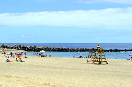 gaurd: Los Cristianos beach, Tenerife, Canary Islands, Spain, Europe - June 13, 2016: Tourists on the beach enjoying the sun