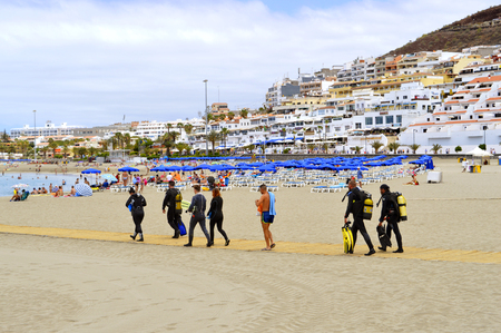 passtime: Los Cristianos beach, Tenerife, Canary Islands, Spain, Europe - June 13, 2016: Scuba divers on the beach walking to the sea