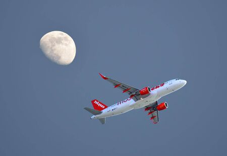 Easyjet Airbus A320 aircraft taking off from Faro Airport with a three quarter moon in the evening sky Stock Photo