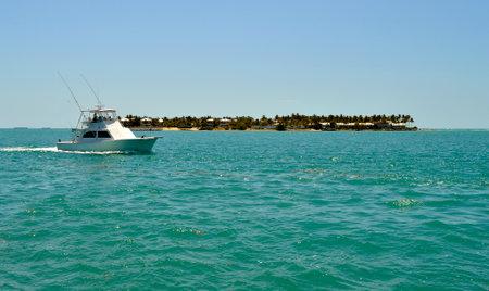Sunset West, Florida Keys, Florida, USA - May 15, 2017 : Fishing boat sailing past Sunset Key in Florida