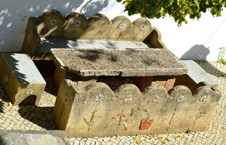 Ancient stone table and chairs in Alte village in the mountains of Portugal