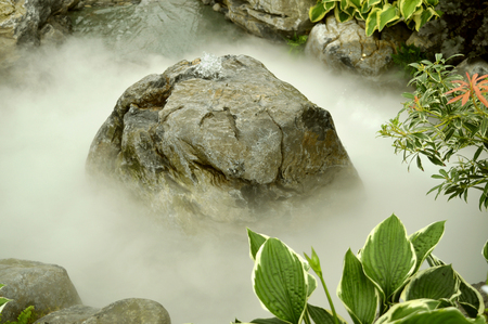 A fountain in a rocky water feature covered in mist