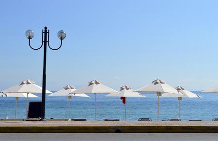 Parasols and lamp on Ipsos Beach in Corfu a Greek island in the Ionian sea