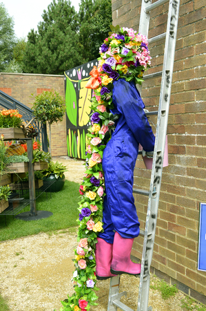 Rapunzel character with flowers used for hair climbing a ladder at the Southport Flower Show